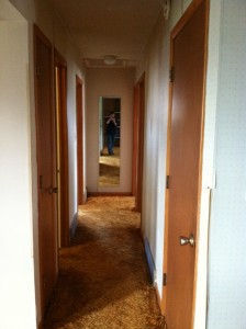 a hallway of doors with a mirror