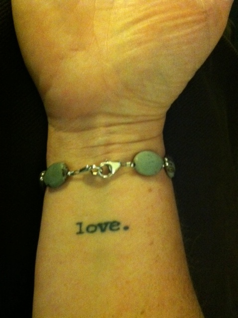 "a tattoo on a woman's wrist that says ""love."""