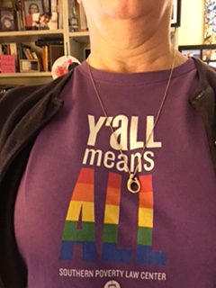 "A woman wearing a t-shirt that says ""Y'all means all."""